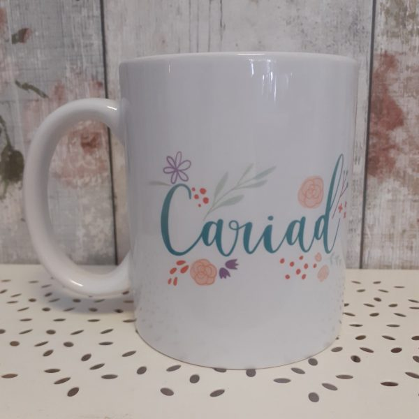 ceramic white mug printed with the welsh word cariad with floral design