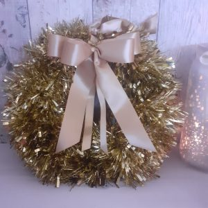 gold tinsel wreath with gold ribbon bow